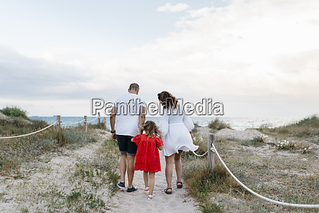 family walking on trail at beach