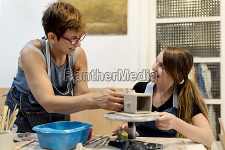 mature woman teaching pottery to coworker