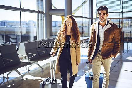 confident business couple standing with luggage