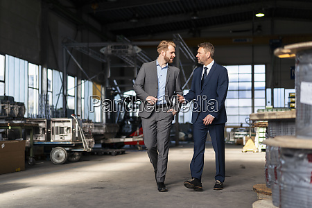 two businessmen walking and talking in