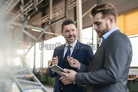 two businessmen with tablet having a