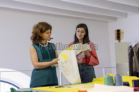 young trainee holding fabric while designer