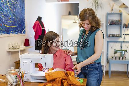 fashion designer supervising trainees sewing skill