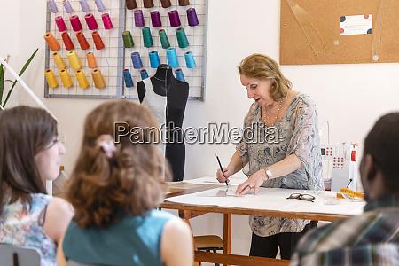 senior designer drawing at workbench while