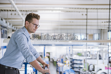 businessman on upper floor overlooking factory