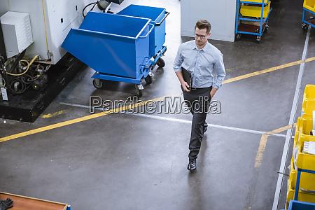 businessman walking in factory