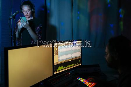 female singer using smart phone while