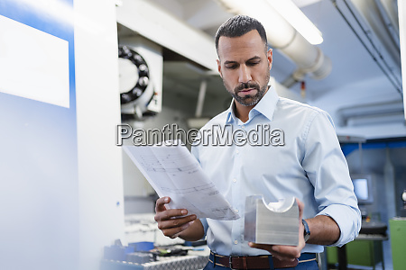businessman holding plan and workpiece in