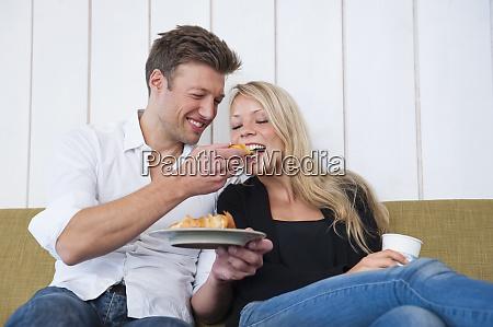 smiling man feeding croissant to girlfriend