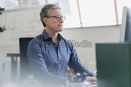 confident mature businessman using computer while
