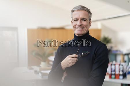 portrait of confident businessman holding eyeglasses