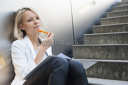 thoughtful businesswoman looking away while sitting