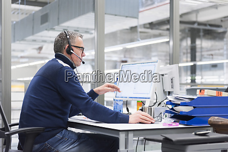 man with headset sitting at desk