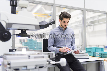 man reading document in a factory