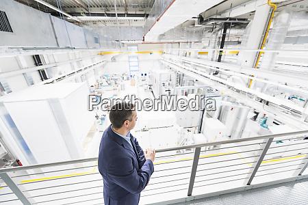 businessman standing on upper floor in
