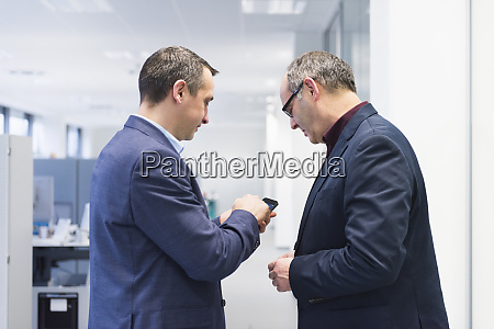 two businessmen sharing smartphone in office
