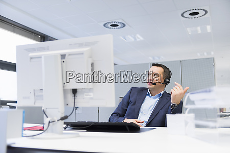 businessman with headset sitting at desk