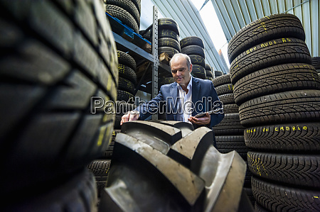 senior male owner examining rubber tire