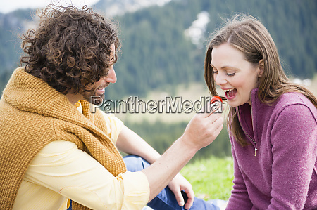 happy man feeding fruit to woman