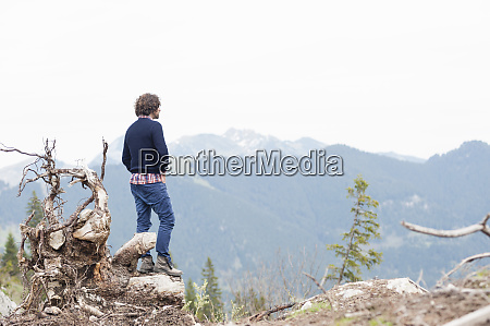 man standing on root while looking