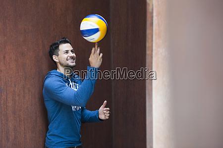 smiling man balancing ball on his