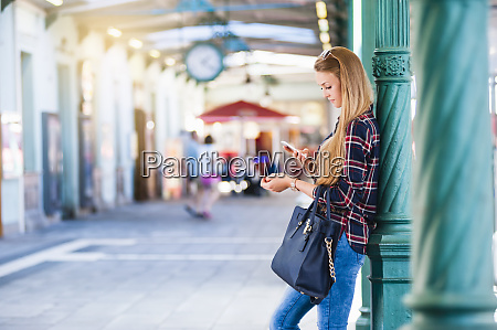 young woman leaning against column looking