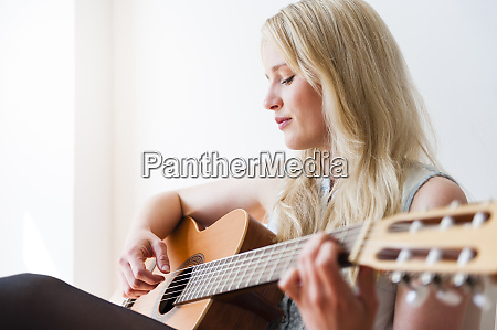 portrait of blond woman playing guitar