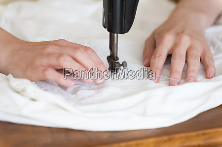 womans hands using old sewing machine