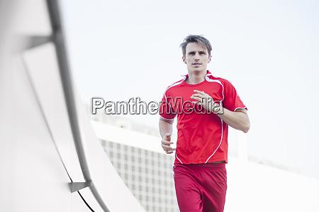 confident mid adult man running against