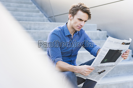 confident handsome businessman reading newspaper while