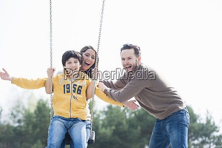 cheerful man pushing mother and son