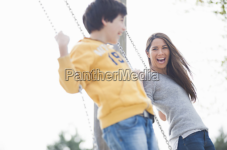 cheerful mother and son swinging at