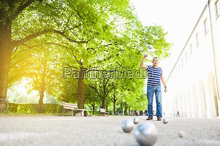 senior man throwing boules ball