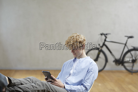 young man sitting using digital tablet