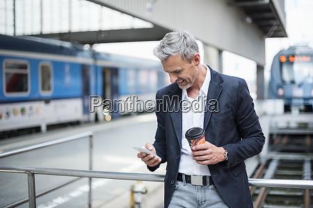 businessman holding coffee using smart phone