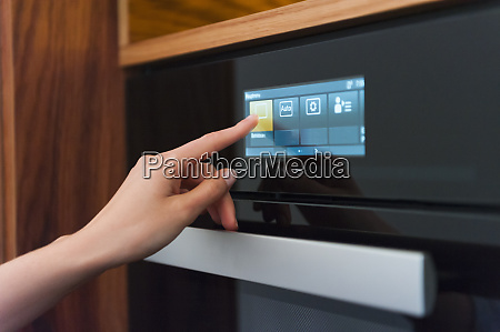 woman hand touching ovens digital display