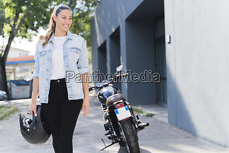 smiling woman with helmet at motorbike