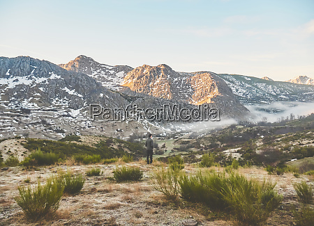 man standing on landscape against rocky