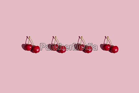 row of fresh cherries on pink