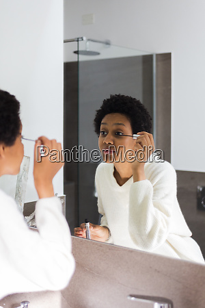 mirror image of young woman applying