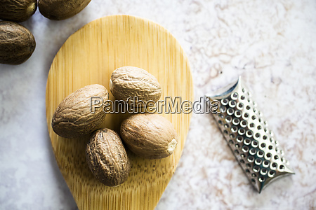nutmeg on wooden spoon and grater
