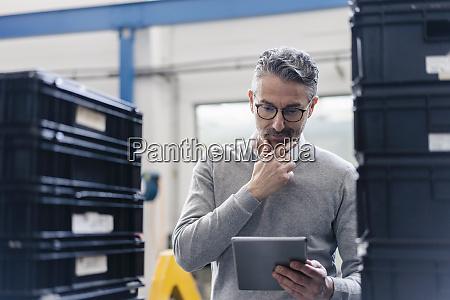 pensive male supervisor using digital tablet