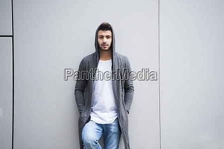 fashionable young man standing against wall