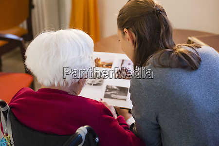 grandmother with granddaughter looking photo album