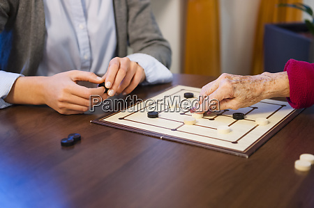 granddaughter playing board game with grandmother