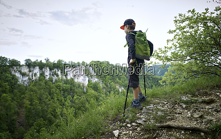 boy standing with hiking poles at