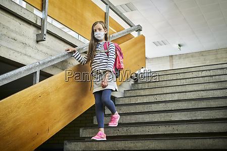 girl wearing mask in school walking