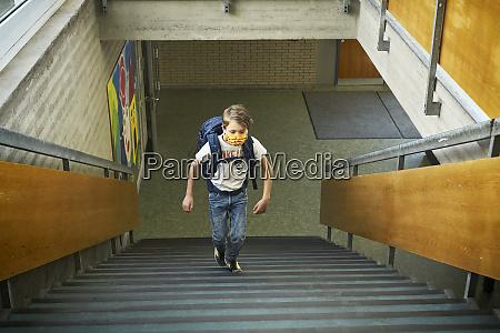 boy wearing mask in school walking