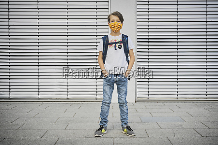 boy with schoolbag wearing mask standing