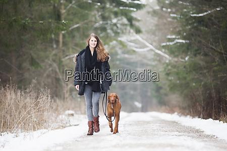 beautiful young woman walking with dog